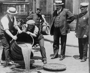 In this photo provided by the Library of Congress, men dump alcohol directly into the sewer system.