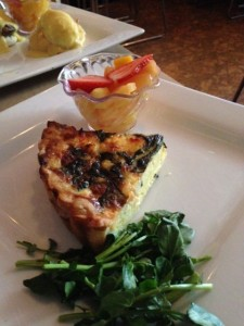 Quiche, served with watercress and a fruit cup.